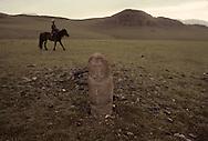 Mongolia. horse riders in frony of  a stone statue (Turkish 6th century)                / cavaliers de la steppe devant une Statue anthropomorphe. Sum de DJARGALAN, dans l'aymag de GOV ALTAY (Granit, VI-VIIIème siecle). / Exemple de l'art monumental des nomades d'Asie Centrale, ce type de statue monolithe, représente une  - 'idole de pierre -  (KUN TCHULUU). D'après la coutume du culte des Ancêtres, cette statue était érigée à la surface d'une tombe d'un noble guerrier, à l'époque des Turcs Célestes. Leur visage présente pratiquement les mêmes caractéristiques : faciès plat, pommettes saillantes, yeux en amandes et moustache. L'idole, vêtue d'une robe avec ceinture, a le bras droit plié au niveau du coude et tient une coupe. Parfois, des oiseaux de passage viennent s'y poser.   / /8    L0006223  /  P0002613