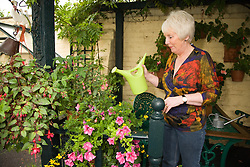 Older woman watering her plants outside,