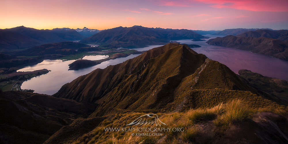 Orange skies bleed into pink as sunset descends over Lake Wakatipu, from Mount Roy in Wanaka, New Zealand