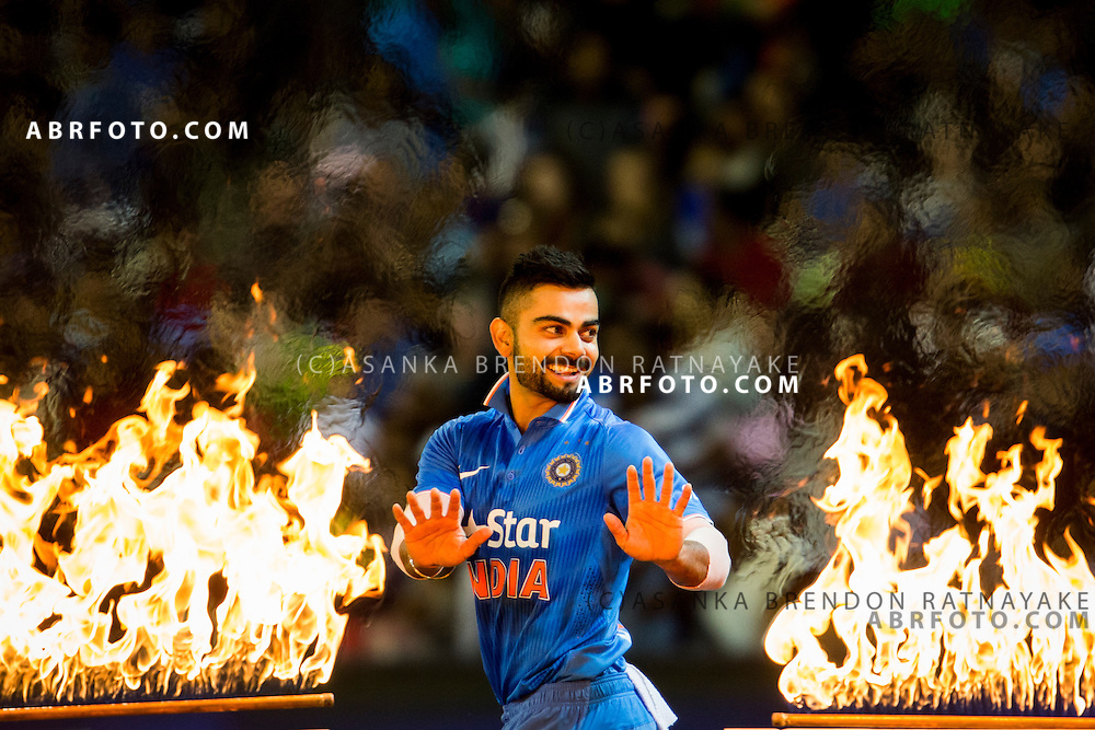 Virat Kohli warms his hands as he walks past the flames during the KFC T20 cricket at the Melbourne Cricket Ground