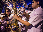 08 SEPTEMBER 2013 - BANGKOK, THAILAND:  People donate money on a replica of Bodhi Tree before a mass alms giving ceremony in Bangkok Sunday. Pinning money to replicas of the Bodhi tree is common in Thai culture. 10,000 Buddhist monks participated in a mass alms giving ceremony on Rajadamri Road in front of Central World shopping mall in Bangkok. The alms giving was to benefit disaster victims in Thailand and assist Buddhist temples in the insurgency wracked southern provinces of Thailand.      PHOTO BY JACK KURTZ