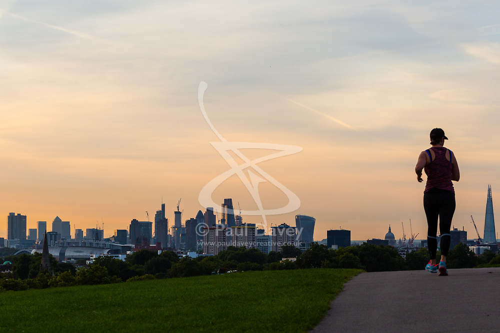 London, August 16 2017 . \A jogger reaches the summit of Primrose Hill as London wakes up to a glorious sunrise. © Paul Davey.