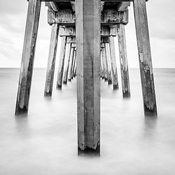 Pensacola Beach Gulf Pier pilings black and white vertical photo. Pensacola Beach is on Santa Rosa Island in the Emerald Coast of the Southeastern United States of America. Copyright ⓒ 2018 Paul Velgos with All Rights Reserved.