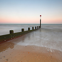 Beach at dawn capturing moving water with sea defences