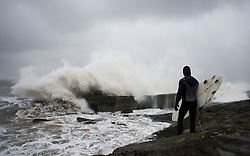 © Licensed to London News Pictures. 21/01/2013..Teesside, England, UK..Surfer Richie Mitchell waits for a lull before taking the plunge to go for a surf as heavy seas pound the Northeast coast on Teesside...Photo credit : Ian Forsyth/LNP.