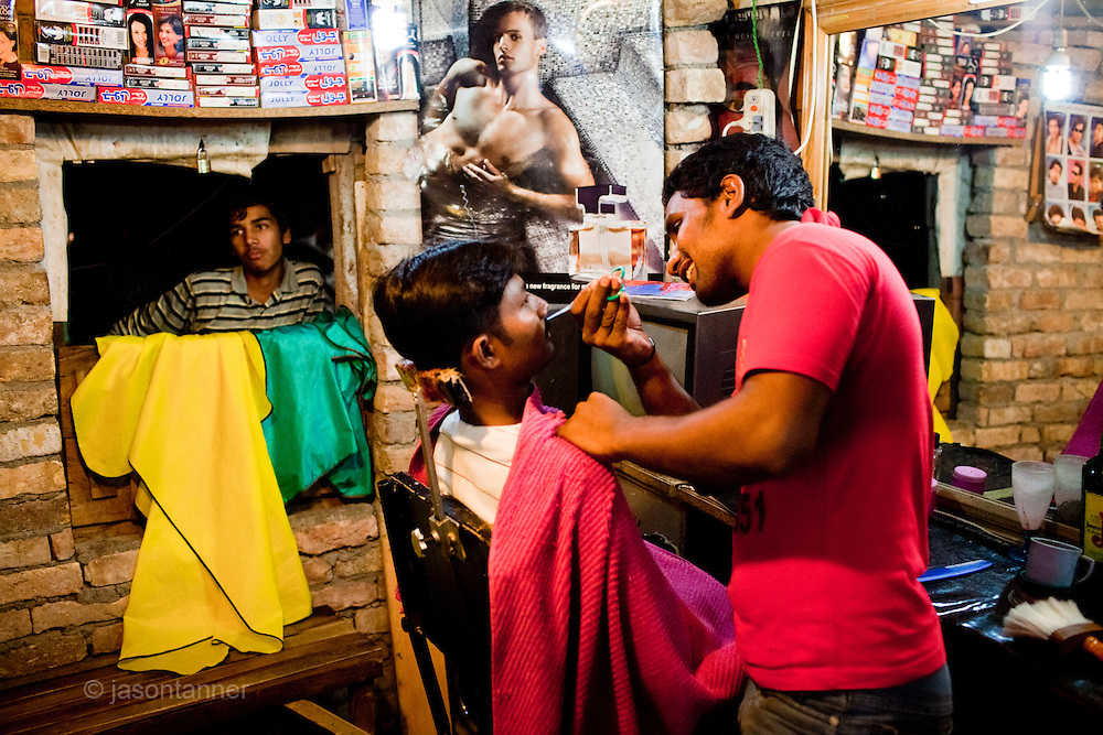 Islamabad: Young men at a barber shop in the colony...Pakistan's Christian communities account for an estimated one percent of the country's 180 million population...I the middle of Islamabad's wealthiest neighbourhood is a 'colony' that's home to some 4000 Christians. Narrow alleys separate multi-storey, squalid houses with open sewers running meandering the alleys to the river that runs through the heart of the colony...Some are recent arrivals from Faisalabad and Gojra, where recent sectarian killings forced many to relocate to the relative safety of the capitol territory. Many are second and third generation residents squatting on land that sees no development assistance from the Capital Development Authority. Power outages are frequent, many residents sleep on the roofs during the long summer months, there are no air-conditioners in the colony...Many of the residents are unemployed; those fortunate to have any income usually work as servants, gardeners, drivers, security guards or cleaners. ..Discrimination against the Christian minorities is rampant in Pakistani society. Many suspect the government of deliberately keeping them at the bottom of the economic ladder to appease the radical religious parties...©JTanner/August2011