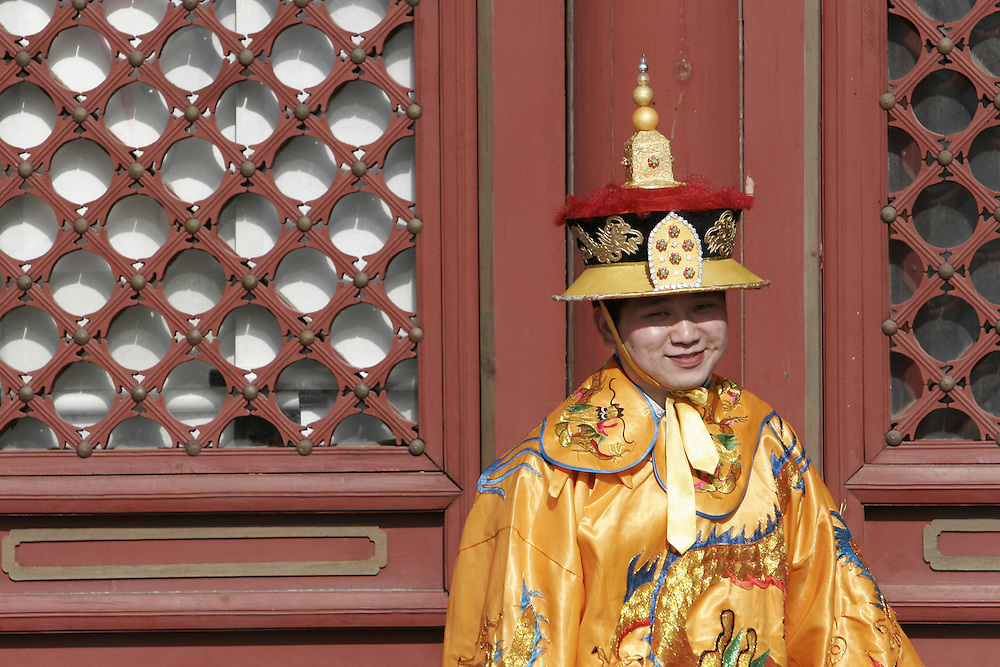 An employee of the Temple of Heaven in south east Beijing, China is dressed in a traditional outfit to entertain the visitors of the temple.