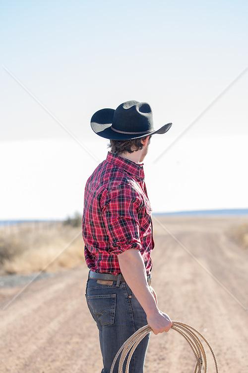 cowboy looking down a dirt road in rural America