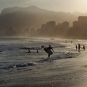 A late afternoon beach scene at Arpoador Beach with Ipanema and Leblon in the distance. Rio de Janeiro, Brazil. 8th August 2010. Photo Tim Clayton.