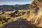 winding road snakes into the distant green hills and rural scene beyond, manaia, coromandel, new zealand