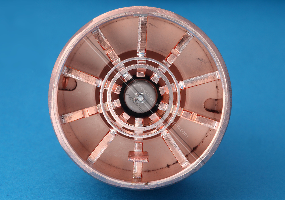 The inside of a magnetron removed from a microwave oven.  The magnetron is a device that creates microwave radiation. A magnetron consists of an electron tube surrounded by a magnet. As electrons are released from the heated cathode they are forced to take a spiral path to the anode by the magnetic field, creating microwaves. This magnetron creates a microwave radiation that is the same frequency as a water molecule vibrates.  When water is exposed to just the right frequency, the water molecules will gain kinetic energy and become hotter.