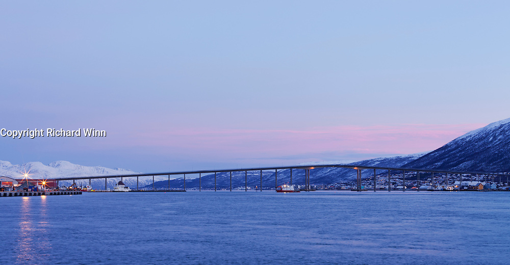View of Tromsø Bridge (Tromsbrua), with the distant mountains and pink-tinged clouds from the sun below the horizon as backdrop.