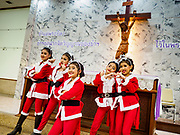 """23 DECEMBER 2018 - CHANTABURI, THAILAND: Girls playing dancing Santas in the Christmas pageant pose for pictures in a chapel at the Cathedral of the Immaculate Conception's Christmas Fair in Chantaburi. Cathedral of the Immaculate Conception is holding its annual Christmas festival, this year called """"Sweet Christmas @ Chantaburi 2018"""". The Cathedral is the largest Catholic church in Thailand and was founded more than 300 years ago by Vietnamese Catholics who settled in Thailand, then Siam.  PHOTO BY JACK KURTZ"""