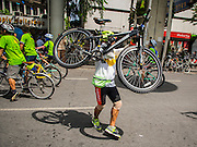 21 SEPTEMBER 2014 - BANGKOK, THAILAND: A bicyclist carries his bike off of Silom Road after participating in a bike rally for Car Free Day in Bangkok. The Thai capital hosted Car Free Day 2014 Sunday. Silom Road, the major thoroughfare in Bangkok's financial district, was closed to cars so bicyclists could use the road. The event was to promote the use of mass transit and environmentally friendly means of transportation. About 20,000 people were expected to participate in a city wide bike riding rally.   PHOTO BY JACK KURTZ