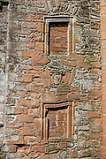 "Windows sealed with bricks. The formidable red sandstone walls of Caerlaverock Castle have a triangular shape, unique in Britain. First built in 1295 to to control trade, its wide moat, twin-towered gatehouse and lofty battlements give Caerlaverock a fairtale appearance, the epitome of a medieval stronghold. In the castle courtyard, walk through Nithsdale Lodging, a remarkable residence built in 1635, ""the most ambitious early classical domestic architecture in Scotland."" Caerlaverock is near Dumfries, on the edge of Caerlaverock National Nature Reserve, in southwest Scotland, United Kingdom, Europe. This stronghold defended the Maxwell family from the 1200s-1640, then was abandoned. It was besieged by the English during the Wars of Scottish Independence, and underwent several partial demolitions and reconstructions from the 1300s-1400s."