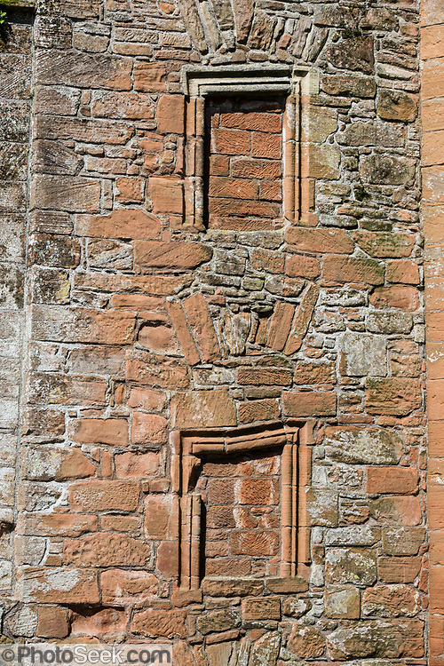 """Windows sealed with bricks. The formidable red sandstone walls of Caerlaverock Castle have a triangular shape, unique in Britain. First built in 1295 to to control trade, its wide moat, twin-towered gatehouse and lofty battlements give Caerlaverock a fairtale appearance, the epitome of a medieval stronghold. In the castle courtyard, walk through Nithsdale Lodging, a remarkable residence built in 1635, """"the most ambitious early classical domestic architecture in Scotland."""" Caerlaverock is near Dumfries, on the edge of Caerlaverock National Nature Reserve, in southwest Scotland, United Kingdom, Europe. This stronghold defended the Maxwell family from the 1200s-1640, then was abandoned. It was besieged by the English during the Wars of Scottish Independence, and underwent several partial demolitions and reconstructions from the 1300s-1400s."""