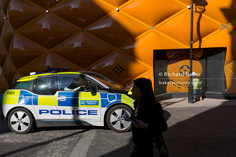 A Zero Emission BMW i3 Met Police patrol car drives past the temporary renovation hoarding of luxury brand Louis Vuitton in New Bond Street, on 25th February 2019, in London, England.
