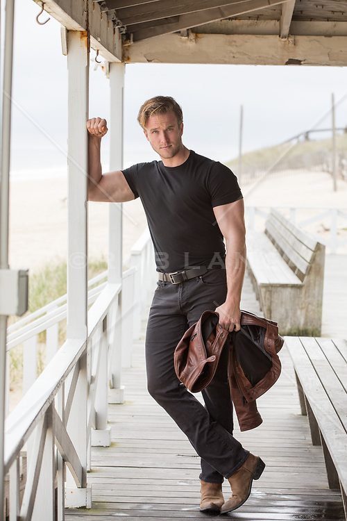 sexy blond man leaning against a post on the ocean
