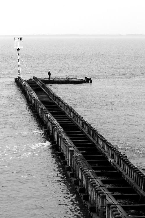 A fisherman on a pier in the harbour of Vlissingen // Een visser staat 's ochtends op een pier in de haven van Vlissingen.