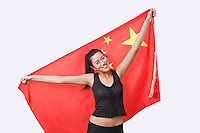 Portrait of smiling young woman holding Chinese flag over white background