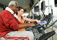 Woman assisting man on exercise bike in gymnasium