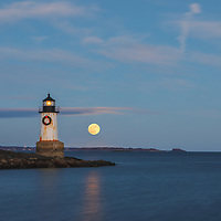 New England lighthouse photography of Fort Pickering Light with full cold moon rising across Winter Island Park in Salem, MA. This iconic Massachusetts lighthouse is located at Winter Island Park in Salem Massachusetts.<br />