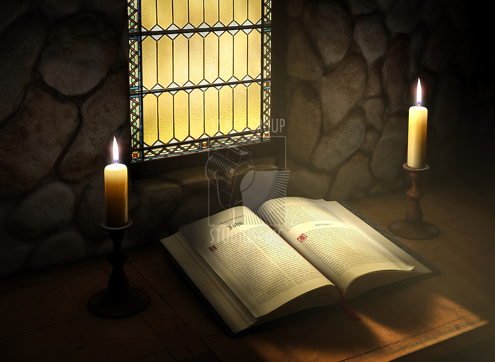 Open Bible flanked with two candles near a sunlit stained glass window in an old monestery