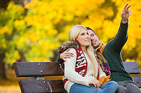 Young man showing something to woman while gesturing in park during autumn