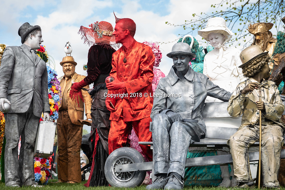 Bancroft Gardens, Stratford-Upon-Avon, Warwickshire, UK. 22nd April 2018.  The winner of the UK's first National Living Statue Championship attracted artists worldwide and thousands of visitors. Stratford-upon-Avon played host to the UK's first National Living Statue Championship as part of the annual Shakespeare's birthday celebrations in the Warwickshire town. A brand-new highlight of the extended three-day extravaganza, the Championship provided an opportunity for professional and junior living statues to pitch against the competition to win a cash prize. The competition ran on the 21st April and Sunday 22nd April and had two categories – professional (first prize £5000) and junior (first prize £50). Professionals needed to complete at least five 45-minute performances over the weekend, with juniors carrying out four 30-minute performances during the Championship. Pictured:  Living statue contestants await the judges' decision in Bancroft Gardens. // Lee Thomas, Tel. 07784142973. Email: leepthomas@gmail.com  www.leept.co.uk (0000635435)
