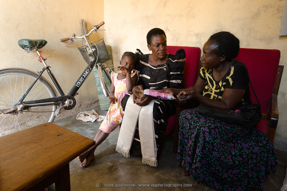 Khana Achieng (right), an Afripads dealer, with Zulie Auma, one of her customers, and Zulie's daughter, Farida Bikobere, at their home near Tororo, Uganda on 2 August 2014.