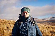 Middle aged man wearing blue raincoat and blue hat looks at camera with snowy Moffat Hills in the background against a blue sky on the Annandale way