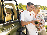 Adult couple standing by jeep man pouring wine smiling