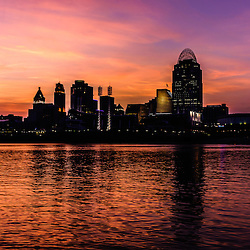 Photo of Cincinnati skyline sunset at night along the Ohio River including Great American Insurance building, Great American Ball Park, US Bank Arena, Scripps building, PNC Tower building, and Carew Tower building. Photo is high resolution and was taken in 2012.