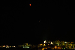 Corigliano Calabro, the total eclipse of Luna, which turns red, on the Church of Sant'Antonio di Corigliano Calabro with Mars a little lower (dot on the right). It is considered the longest eclipse of the century as it lasts 103 minutes and you can also see near the planet Mars that will shine.