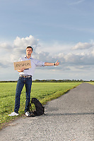 Full length of young man hitching while holding anywhere sign on countryside
