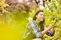 Portrait of mature beautiful gardener examining plants