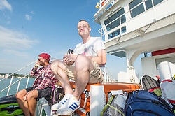 © Licensed to London News Pictures. 11/06/2015. East Cowes, UK.  Festival goers travelling to Isle of Wight Festival 2015 on the Southampton-East Cowes ferry early on thursday morning.  This years festival include headline artists the Prodigy, Blur and Fleetwood Mac.  Photo credit : Richard Isaac/LNP