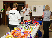 """Church Co-Council Sandy Brallier, Associate Pastor Paula Gile and Church Council Moderator John Walker welcomes volunteers Wednesday morning as the first week of the """"Got Lunch"""" program gets packed up for delivery at the Congregational Church in Laconia.  (Karen Bobotas/for the Laconia Daily Sun)"""
