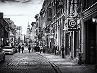 La Cage, Bilodeau, St Paul pub and other shops and restaurants on Rue St Paul historic street of old town in Montreal, Quebec, Canada at sunset. Rue Saint Paul Est, Ville de Montréal, Québec, Canada. Black and white.