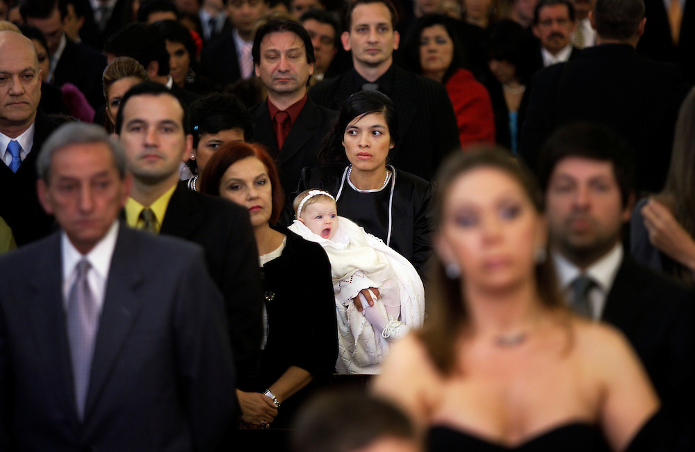 Carpeta 18 Foto 04<br /> Una empleada domestica sostiene un bebe en medio de los concurrentes a la ceremonia religiosa de un casamiento en Asuncion, Paraguay el 28 de setiembre de 2009. (Jorge Saenz)<br /> <br /> &quot;Todo era una Fiesta&quot;:<br /> Por mas crisis que ataquen la econom&iacute;a publica y privada, la clase alta de Paraguay tal como la de otros pa&iacute;ses, no limita en lo mas m&iacute;nimo su costumbre de festejar las bodas con una gran inversi&oacute;n econ&oacute;mica en los eventos. Este trabajo presentado es parte de uno mas general en desarrollo sobre la sociedad paraguaya llamado &quot;Las Clases&quot; desde hace mas de 10 a&ntilde;os.
