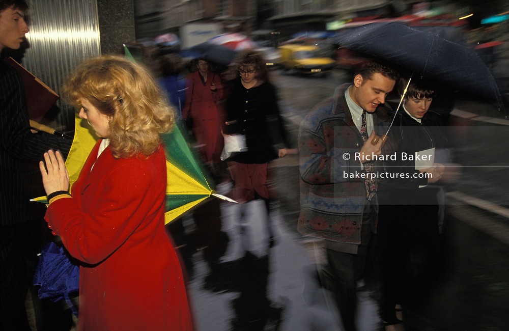 City of London office workers dodge the rain under umbrellas in a darkening street, on 22nd March 1993, in London, England.