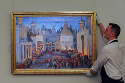 """© Licensed to London News Pictures. 02/06/2017. London, UK. A technician presents """"The Kremlin at Night on the Eve of the Coronation of Tsar Mikhail Fedorovich"""", 1914, by Konstantin Yuon. (Est. 400-600k).  Preview of Sotheby's sale of Russian pictures and works of art which takes place on 6 June 2017 at Sotheby's in New Bond Street. Photo credit : Stephen Chung/LNP"""