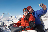 Couple sitting on snowmobile in snow photographing selves with digital camera.