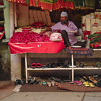 Seller of flowers and sweets, to be used as offerings in the tomb  Nizamuddin Auliya inside, bellow him are the shoes of some who entered the temple.