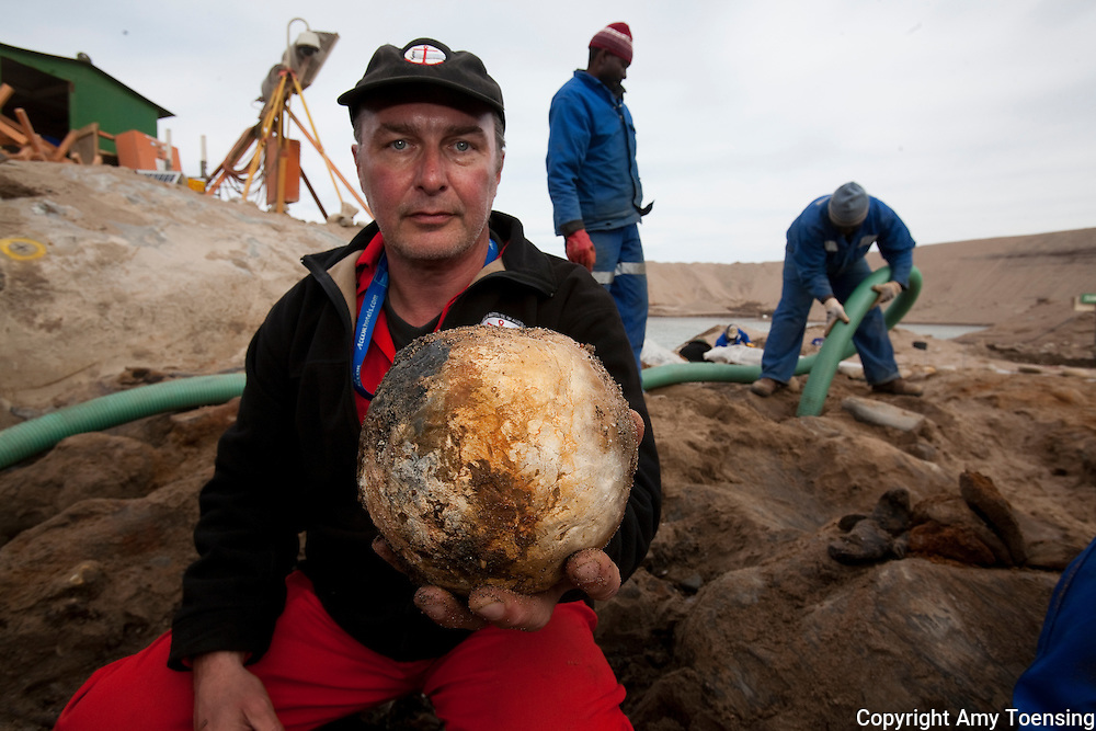 ORANJEMUND, NAMIBIA -- SEPTEMBER 24: Head archeologist Bruno Werz holds a stone canon ball, used as anti-personal, from the site of the wreck on September 24, 2008 in Oranjemund, Namibia. The wreck was discovered by miners in the Namdeb diamond mine off the coast of Namibia. The ship was found seven meters below sea level on April 1, 2008. Archeologists presume the wreck is from the early 1500s. Most of the the artifacts found are being stored in a storage shed at the Namdeb Diamond Mine. Items include: copper ingots, bronze canons, canon balls, pewter bowls and plates, ivory tusks from African elephants, and most substantial over 2000 gold coins- approximately 21 kg - the most gold found in Africa since the Valley of the Kings in Egypt. (Photo by Amy Toensing) _________________________________<br /> <br /> For stock or print inquires, please email us at studio@moyer-toensing.com.