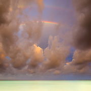 Multiple rainbows build with storm clouds over the emerald green waters of the Caribbean Ocean in Playa del Carmen Mexico.