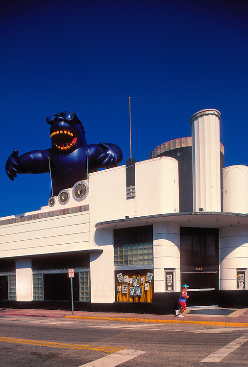 On Halloween day in South Beach, a huge, blow-up, King-Kong-iike ape  with sunglasses towers over a jogger and a landmark Art Deco building -- a Streamline Moderne masterpiece, originally Hoffman's Cafeteria, designed in 1939 by architect Henry Hohauser.