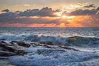 The sun rises through clouds over the ocean at Reid State Park, radiating golden rays of light as the waves crash below.