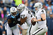 NASHVILLE, TN - NOVEMBER 29:  Derek Carr #4 gets help from the blocking of Austin Howard #77 of the Oakland Raiders during a game against the Tennessee Titans at Nissan Stadium on November 29, 2015 in Nashville, Tennessee.  The Raiders defeated the Titans 24-21.  (Photo by Wesley Hitt/Getty Images) *** Local Caption *** Derek Carr; Austin Howard