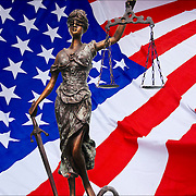 American Flag symbol of United States of America, the red white and blue with a statue of Blind Justice in front of it.<br /> <br /> American Flag - GOR-84121-11<br /> Blind Justice - GOR-64520-08